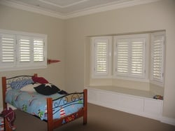 A children room with small bed and windows installed with security shutters