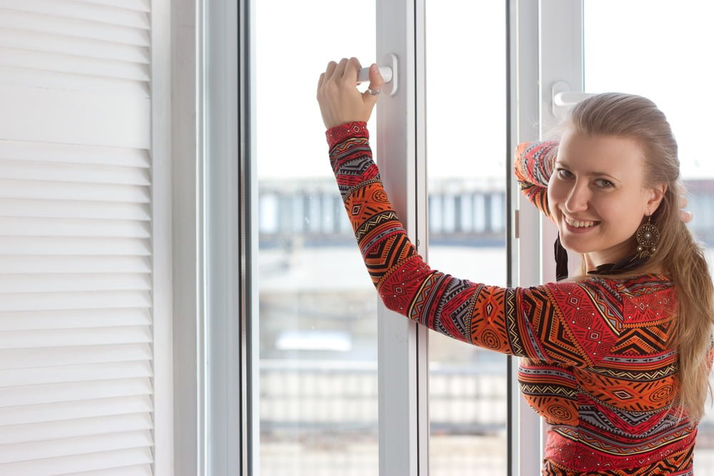 Woman opening security window from inside