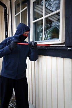 A thief covering his face trying to break a house window with a rod
