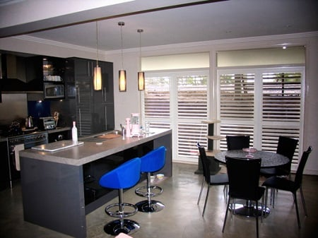 An interior of dining area with kitchen, dinning table and doors installed with aluminium shutters