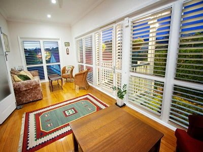 Living room installed with plantation door and window shutters