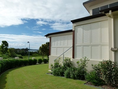 Beautiful outer view of a modern bungalow with window and doors installed with plantation shutters