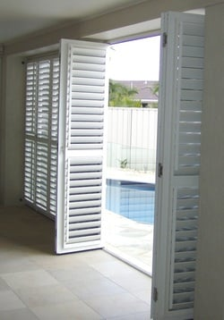 Aluminium Plantation shutter doors installed at the entry of swimming pool area