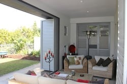 A modern living room installed with open plantation shutter doors