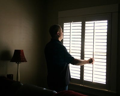 A middle aged man standing near plantation shutter window of a room
