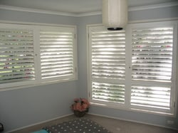 A corner of room installed with plantation window and door shutters