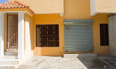 A house with grill windows, door and a shop with aluminium security shutter