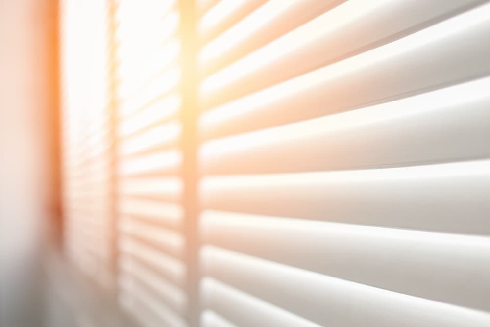 White wooden blind with sunlight