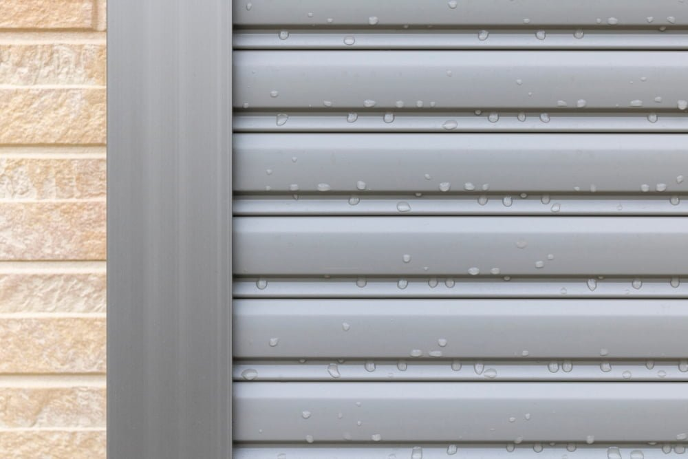 Silver window shutter that has become wet by rain