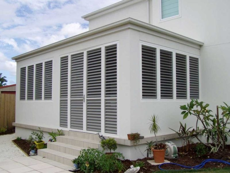 Outdoor view of house installed with patio enclosure shutters