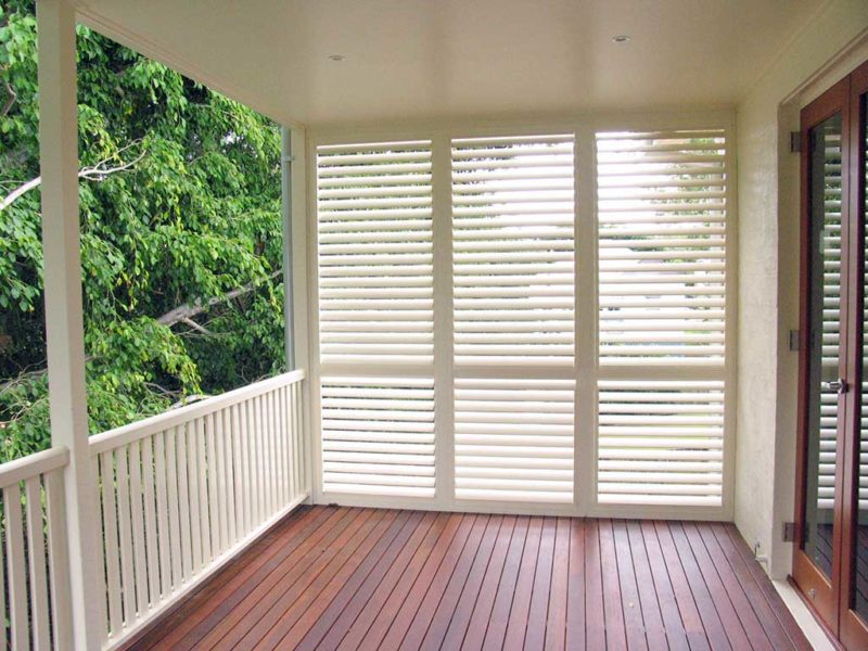Patio enclosure shutters installed on one side of the balcony area
