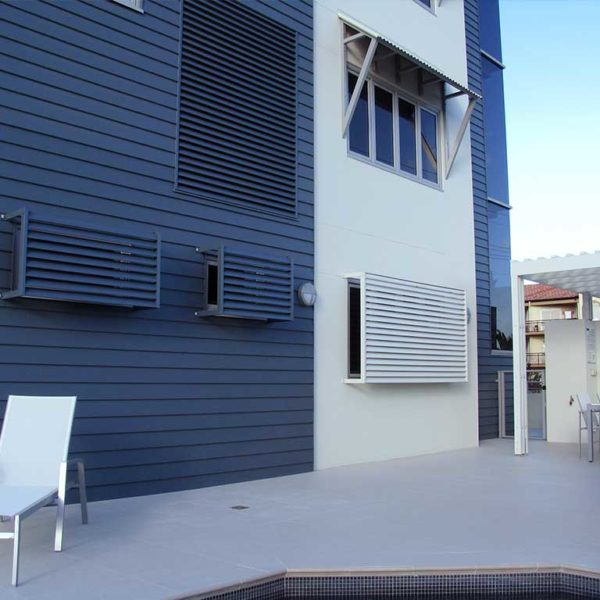 Blue and white painted building installed with privacy screens on windows