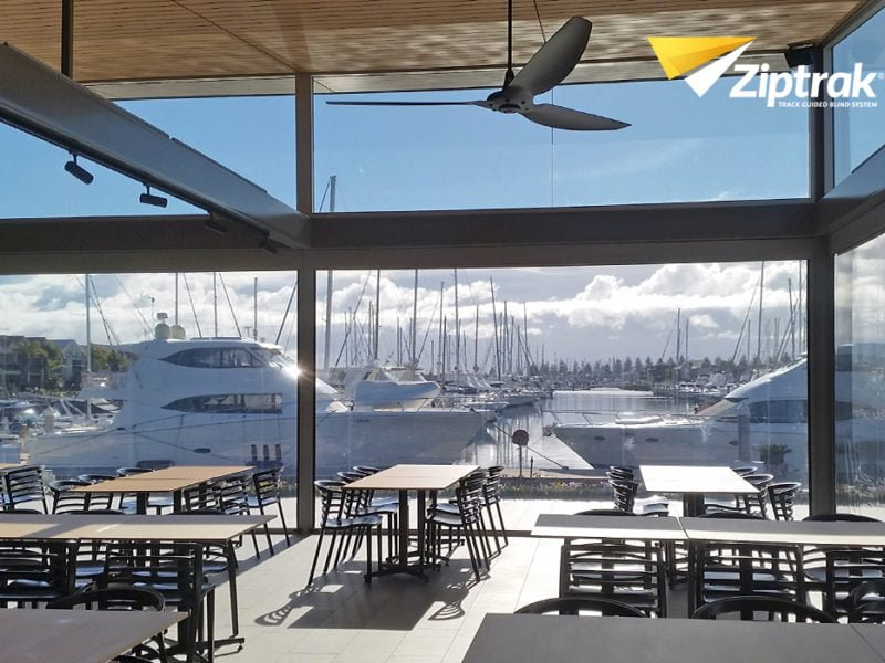 Inside view of Yacht club restuarant with a yacht parked in port