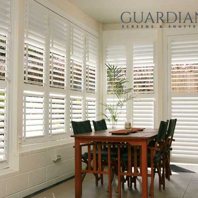 Image of Aluminium shutter windows in dinning are with Guardian Screens & Shutters logo