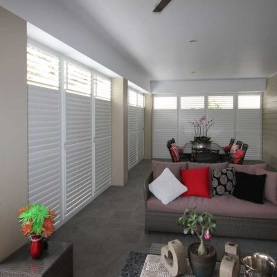 A modern room with closed patio enclosure shutters windows and doors
