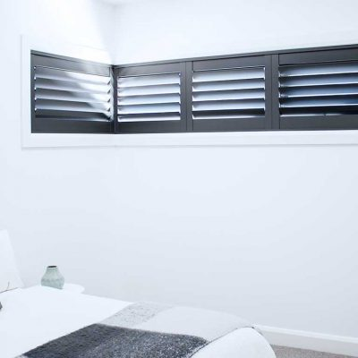 Interior view of bedroom installed with Black ThermoPoly Shutters