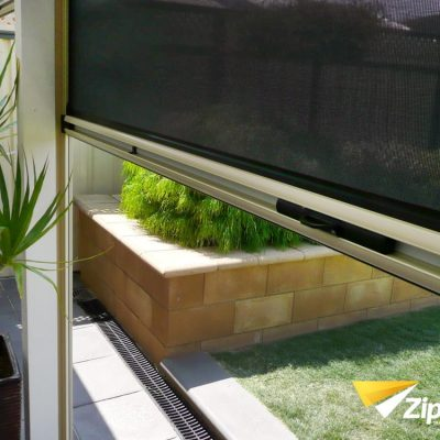 Half open ziptrak blind on window with garden view