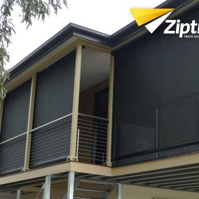 Black blinds installed on the windows of a modern house with Ziptrack logo