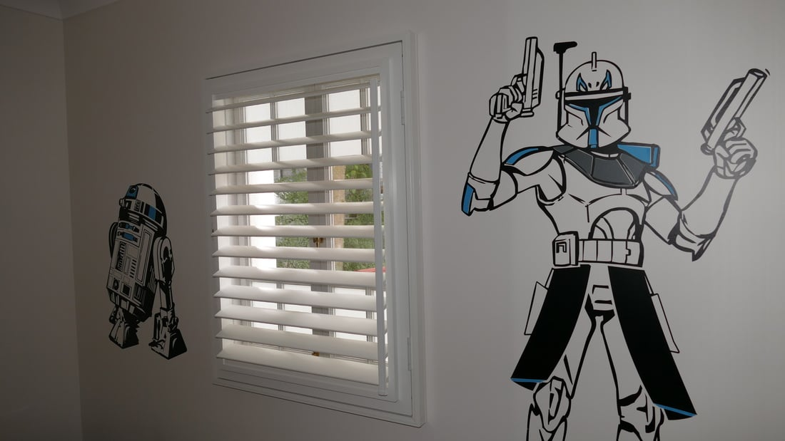 Kids room with wall filled with funky wallpaper and window with white shutter