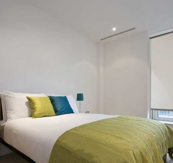 Interior of modern bedroom with a bed and windows installed with Ziptrak indoor blinds